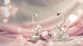 Crystal or glass swans with a diamond on pink cloth. Surrounded with hearts bokeh Royalty Free Stock Photo