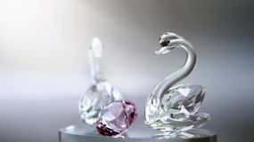Crystal glass swans with a pink diamond. Crystal glass swans with a pink diamond Stock Photos