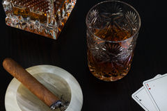Crystal glass of whisky and a cigar. On a dark background Royalty Free Stock Images