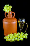 Crystal glass with white wine, bottle and bunch of white grapes Royalty Free Stock Photography
