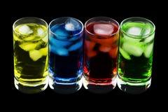 4 Crystal Glasses avec 4 boissons colorées différentes de froid Photographie stock libre de droits