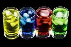 4 Crystal Glasses con 4 diversas bebidas coloreadas del frío Imagenes de archivo