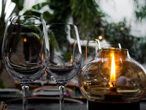 Crystal glasses lit by a candle Stock Images
