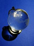 Crystal globe. Small crystal earth globe over blue background Royalty Free Stock Photography