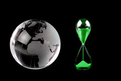 Crystal globe and green hourglass on black background Royalty Free Stock Images