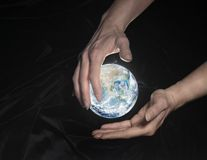 Crystal globe and hands Royalty Free Stock Photography