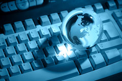 Crystal globe on keyboard. Toned crystal globe on computer keyboard concept for global business or communications Royalty Free Stock Images