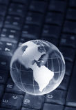 Crystal globe on keyboard Stock Photos