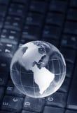 Crystal globe on keyboard stock photos