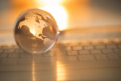 Crystal Globe On Keyboard. Close-up of crystal globe on keyboard with orange light in background Royalty Free Stock Photos