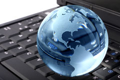 Crystal globe on laptop. Blue glass globe on a laptop keyboard royalty free stock photo