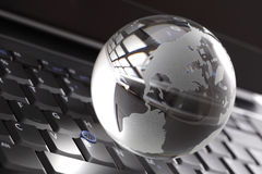 Crystal globe on laptop keyboard Stock Photo