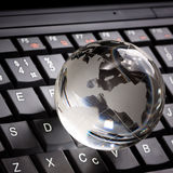 Crystal globe on laptop keyboard Royalty Free Stock Photos