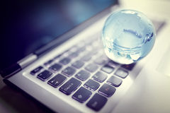 Crystal globe on laptop keyboard Royalty Free Stock Photography