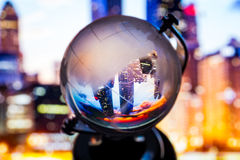Crystal globe reflection. Crystal globe with blur background and reflection of cityscape and landscape inside Stock Photos
