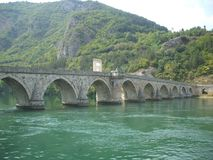 The Bridge on the Drina. Crystal green water of river Drina and the famous bridge from a novel The Bridge on the Drina written by Ivo Andric royalty free stock images