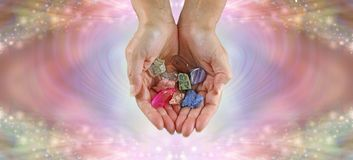 Crystal healer offering selection of tumbled healing stones stock photography