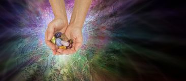Crystal Healer Offering Set of Chakra Crystals. Female therapist holding a set of chakra crystals against a radiating multi-coloured paua shell mosaic background stock photo