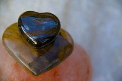 CRYSTAL HEALING HEARTS. HEMATITE TIGER EYE RESTING ON QUARTZ STACKED IN HIMALAYAN SEA SALT AND ONYX Stock Photography