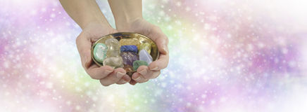 Crystal healing therapist website header. Female crystal healer holding and offering brass dish with selection of healing crystals on pastel rainbow colored Stock Image