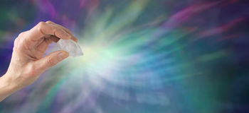 Crystal healing website banner. Crystal Healer holding terminated quartz with a blue and purple background and energy display Royalty Free Stock Photography