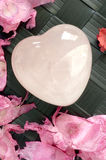 Crystal heart 2. Crystal heart surrounded by petals Royalty Free Stock Photos