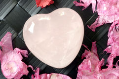 Crystal heart. Surrounded by petals Royalty Free Stock Photos