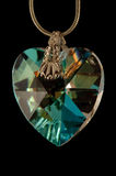 Crystal heart closeup. Necklace made from mountain crystal on black background royalty free stock images