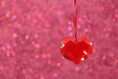 Crystal Heart Pendant. A red glass heart pendant hanging in front of a pink bokeh background Royalty Free Stock Photo