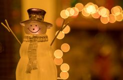 Crystal Holiday Snowman Ornament Sitting in Front of a Decorated Fireplace Mantle. Picture of a crystal snowman ornament sitting in front of a Christmas time royalty free stock photo