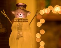 Crystal Holiday Snowman Ornament Sitting in Front of a Decorated Fireplace Mantle. Picture of a crystal snowman ornament sitting in front of a Christmas time stock photography