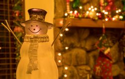 Crystal Holiday Snowman Ornament Sitting in Front of a Decorated Fireplace Mantle. Picture of a crystal snowman ornament sitting in front of a Christmas time royalty free stock image