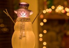 Crystal Holiday Snowman Ornament Sitting na frente de um envoltório decorado da chaminé imagem de stock