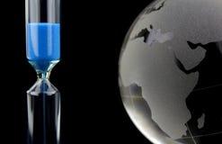 Crystal jordklot och blått timglas Arkivbilder