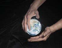 Crystal jordklot och händer Royaltyfri Fotografi