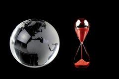 Crystal jordklot och rött timglas på svart bakgrund Royaltyfri Bild