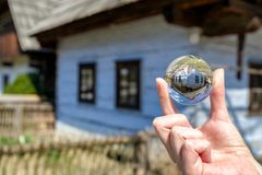Crystal lensball and folk architecture in musem of the Slovak village. Crystal lens ball and old rural house in musem of the Slovak village. Folk architecture stock photos