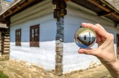 Crystal lensball and rural cottages in musem of the Slovak village. Crystal lens ball and old rural cottage in musem of the Slovak village. Folk architecture royalty free stock photos