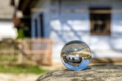 Crystal lensball and rural cottages in musem of the Slovak village. Crystal lens ball and old rural cottage in musem of the Slovak village. Folk architecture stock photography