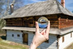 Crystal lensball and rural cottages in musem of the Slovak village. Crystal lens ball and old wooden cottage in musem of the Slovak village. Folk architecture royalty free stock photography
