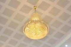 Crystal lighting fixture illuminating on ceiling. Stock Photos