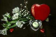 Crystal ljusstake, bukett från vita blommor och choklader i röd askhjärta Royaltyfria Bilder