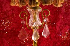 Crystal on old Victorian lamp. A view of glass crystal on an old antique Victorian lamp with a red velvet background and sequins Stock Photography