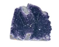 Crystal pendant on silver chain presented on amethyst geode Stock Photo