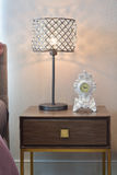 Crystal reading lamp and classic clock on bedside table. In cozy bedroom interior Royalty Free Stock Photos