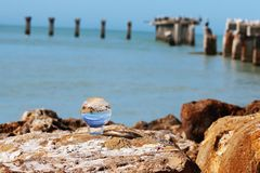 Crystal reflective ball on rocks at beach. With broken pier and birds stock images