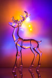 Crystal reindeer statuette in front of colorful Aurora. With reflections Royalty Free Stock Photos