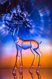 Crystal reindeer statuette in front of colorful Aurora. With reflections Stock Photography