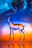 Crystal reindeer statuette in front of colorful Aurora. With reflections Stock Image