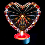 Crystal ribbed heart illuminated with candle. On black background Stock Image